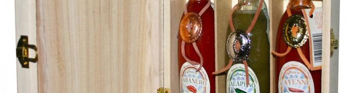 Billedet viser de tre flasker med stærk chilisauce i trækassen.